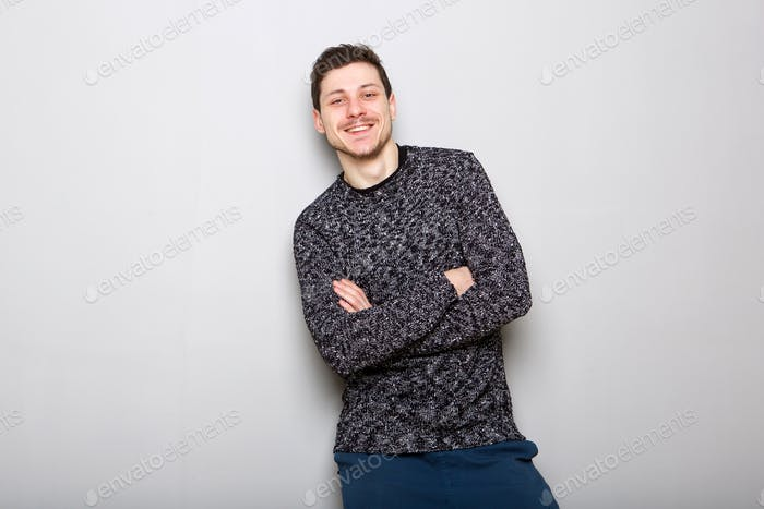 happy young man standing against gray wall