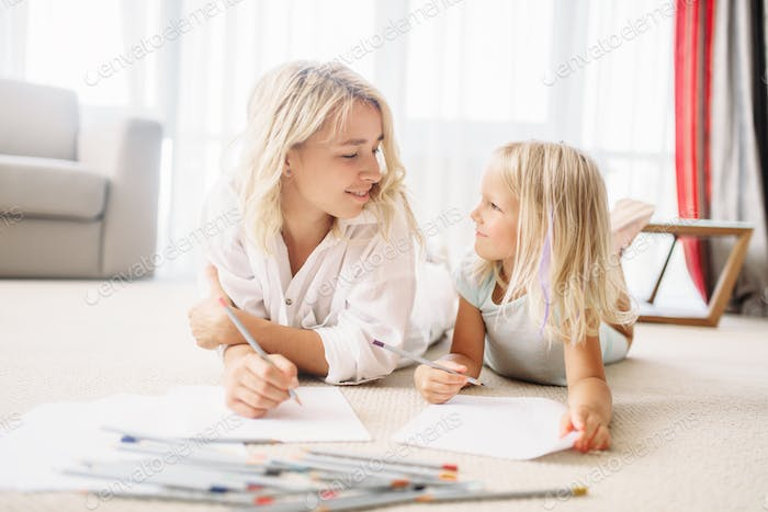 Mother and child draw lying on the floor