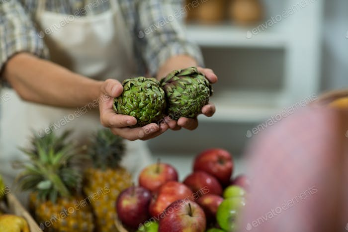 Vendor offering custard apples to the woman at the counter