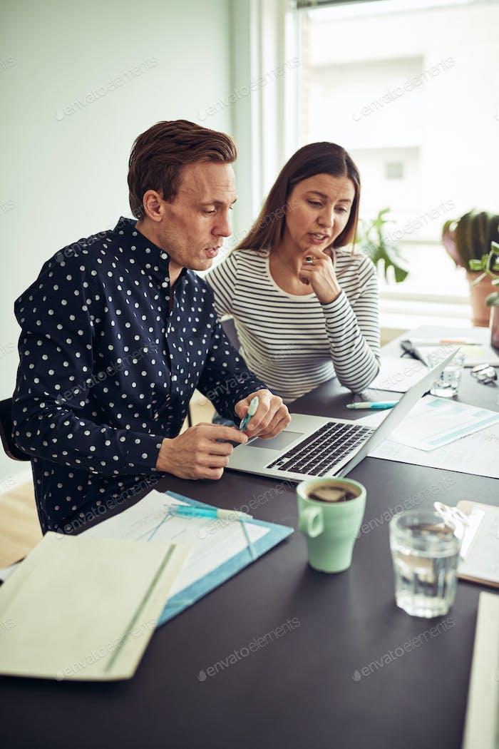 Zwei Arbeitskollegen verwenden einen Laptop zusammen in einem Büro