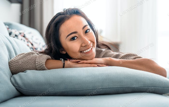 Relaxed asian girl lying on sofa at home in calm leisure time