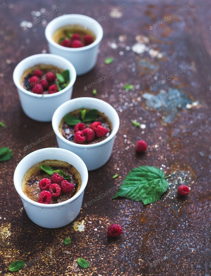 Creme brulees with raspberries and mint in white bowls over grunge metal backdrop. Top view