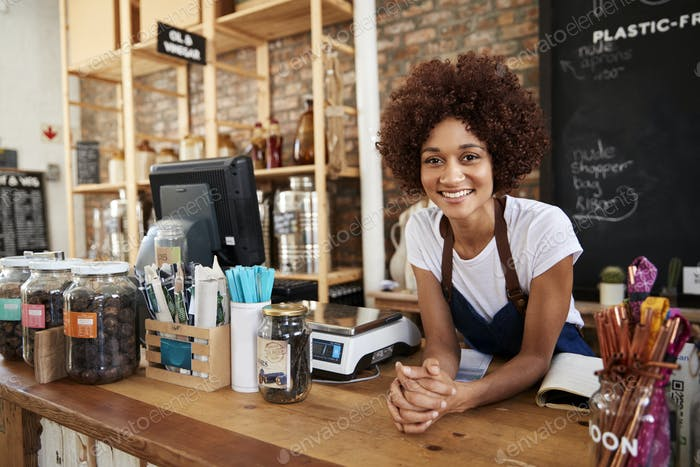 Portrait Of Female Owner Of Sustainable Plastic Free Grocery Store Behind Sales Desk