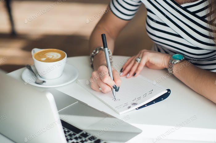 A white blank notebook with a luxury pen and a cup of Latte coffee with blurred laptop in the
