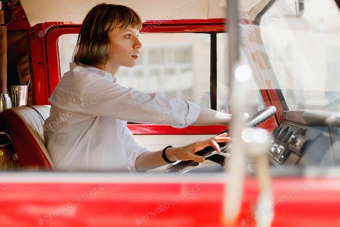 Junge Frau in weißem Hemd gekleidet sitzt am Steuer eines leuchtend roten Minivans