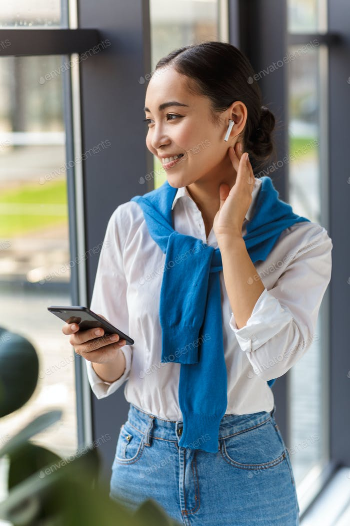 Image of asian woman wearing earbuds holding cellphone by window