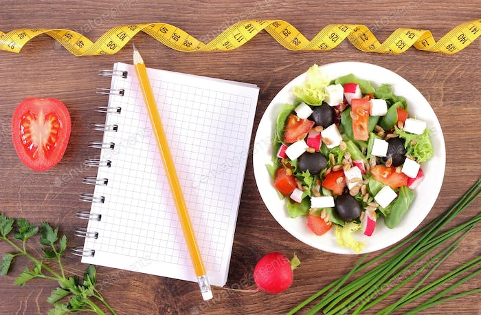 Fresh prepared greek salad with vegetables, tape measure and notepad for writing notes