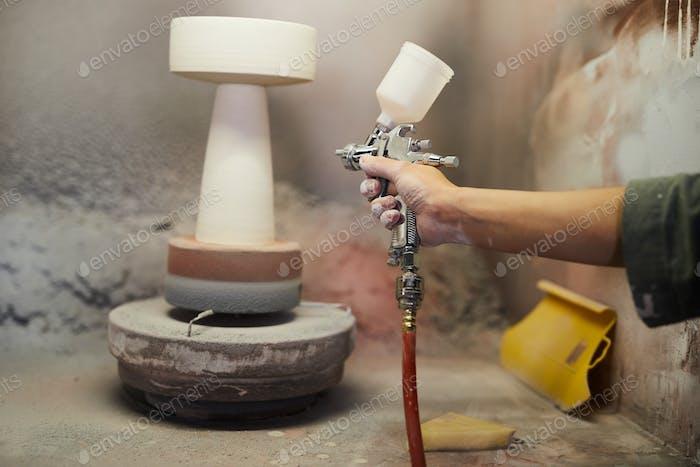 Painting ceramic piece with sprayer