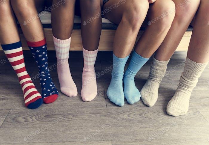 Nahaufnahme von vier Paaren von Beinen mit Socken