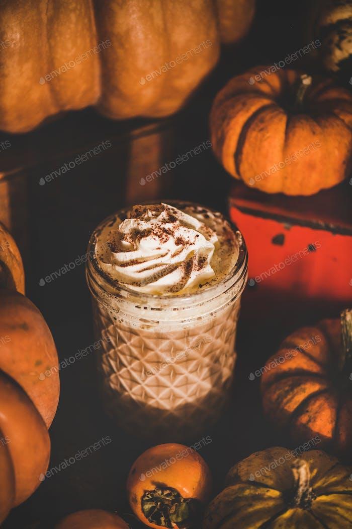 Kürbis Gewürz Latte Kaffeegetränk im hohen Glas unter Kürbissen