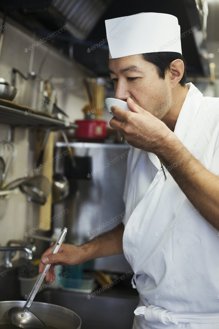 Chef working in the kitchen of a Japanese sushi restaurant, tasting food.