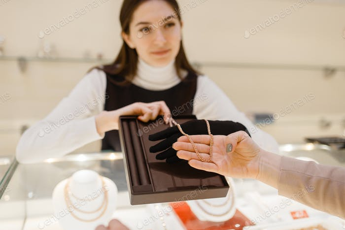 Woman choosing golden chain in jewelry store