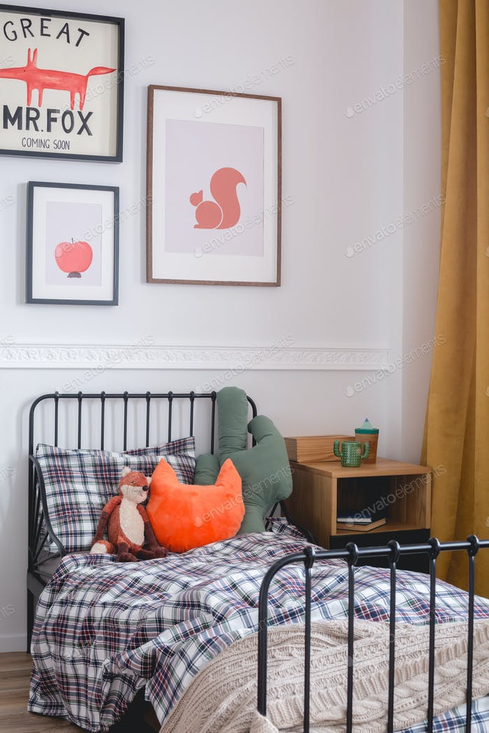 Pillows and toys on single metal bed in vintage bedroom interior for kid