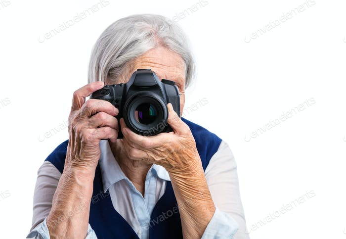 Senior woman shooting with a digital camera over white