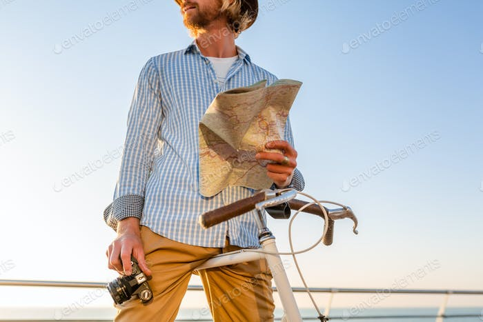 young attractive man traveling on bicycle by sea