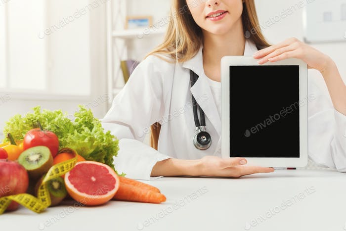 Doctor nutritionist and holding digital tablet