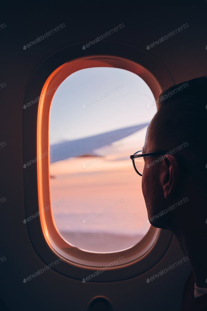 Man looking throught window of airplane