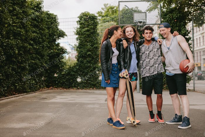 Teenage friends with skateboard and basketball