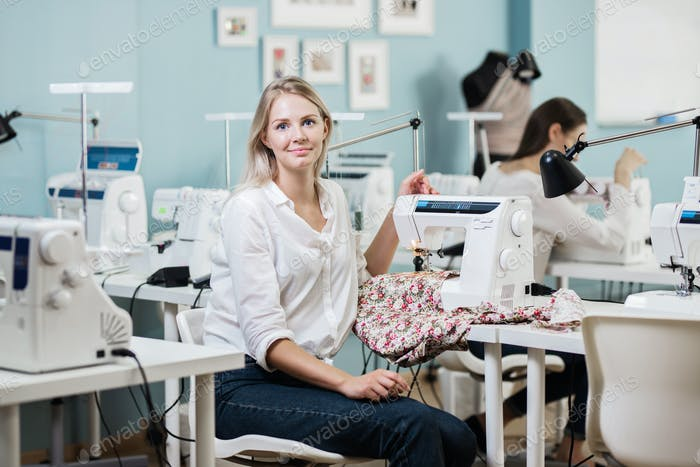 A smart-looking pretty blond woman wearing white shirt is sewing with the electric sewing-machine