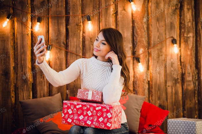 Pretty woman taking selfie photo on mobile phone near decorated christmas wall with light bulbs