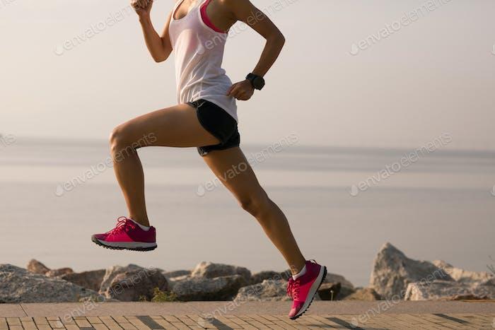Sportswoman running on seaside trail