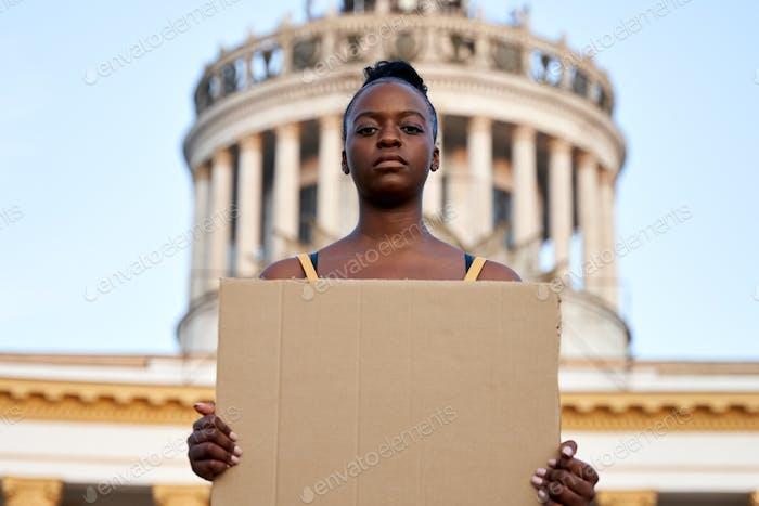 Jóvenes activistas africanas de pie al aire libre sostener cartel vacío protestando en la calle.