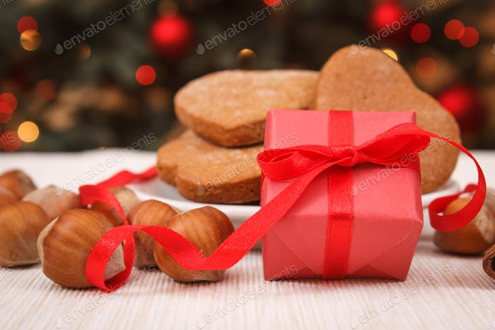Wrapped gift, gingerbreads and christmas tree with lights in background
