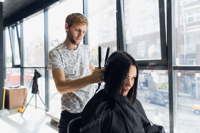 Beautiful woman happy while hairdresser is straightening her hair in salon. New haircut or hairstyle