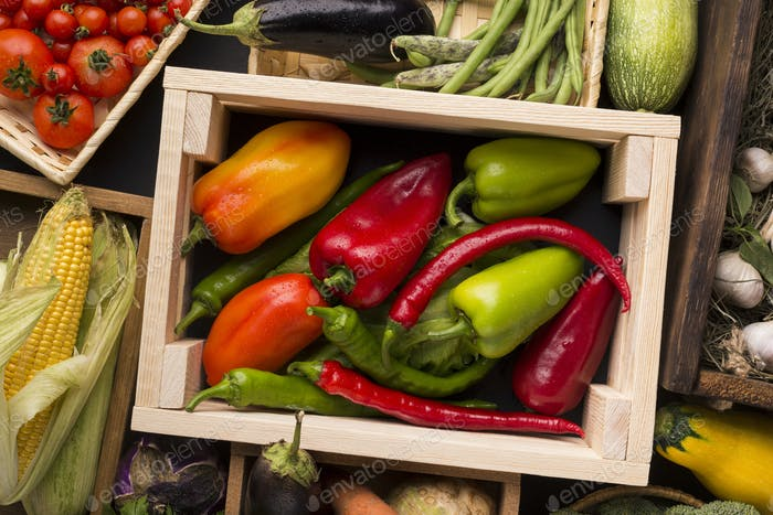 Different red green farm peppers in wooden box
