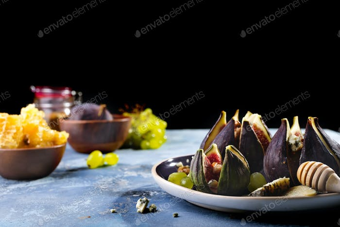 Figs appetizer with cheese, walnut and honey on ceramic plate and blue concrete background
