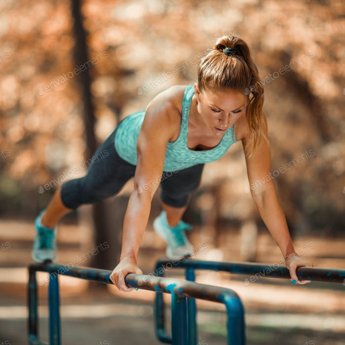 Woman Exercising on Parallel Bars Outdoors in The Fall