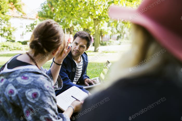 Freelancers discussing at park
