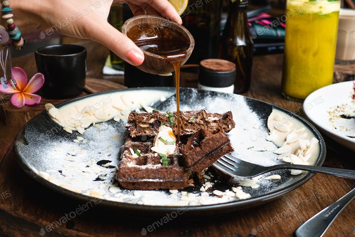 Pouring maple syrup on chocolate waffle