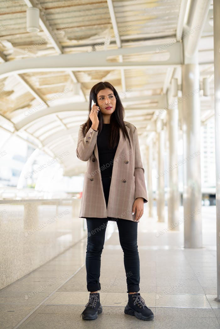 Full body shot of young beautiful Indian businesswoman talking on the phone in the city