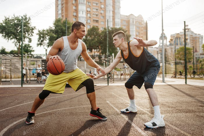 Dos jugadores en el centro del campo de baloncesto