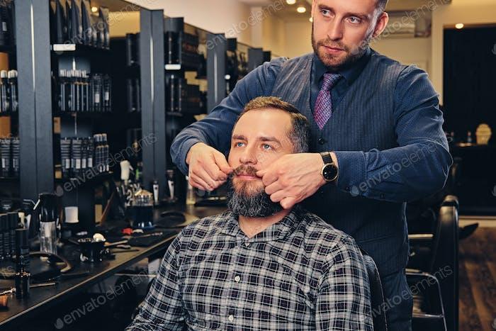Стильный мужской парикмахер делает стрижку для бородатого мужчину в парикмахерской.