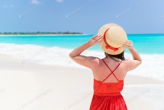 Young woman in hat during tropical beach vacation. Back view of beautidul girl outdoors
