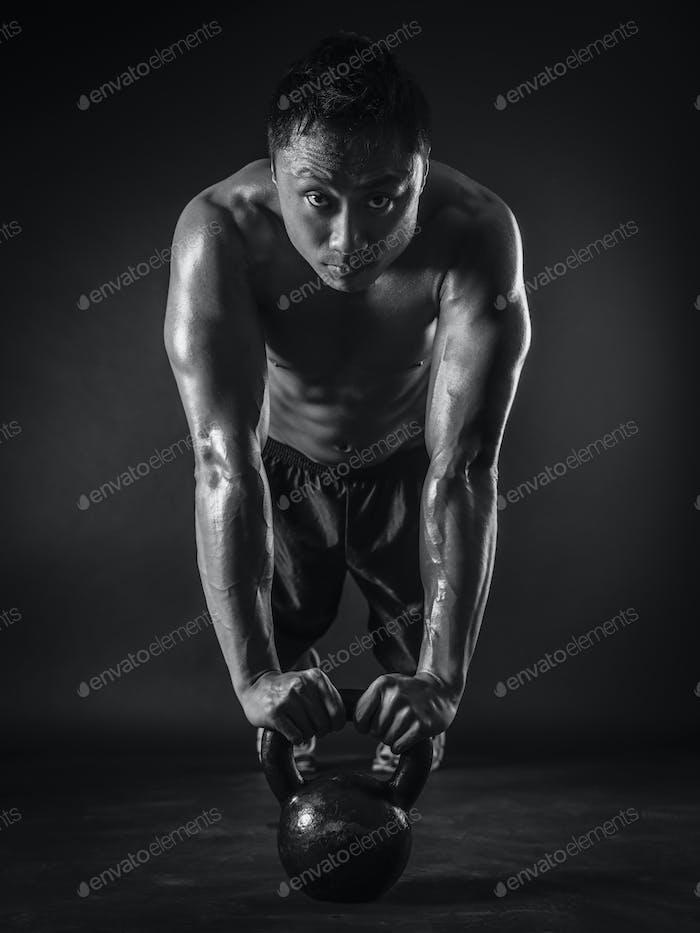 Muscular man doing pushups with kettlebell