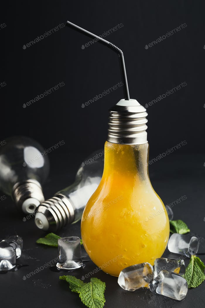 Cold cocktail in light bulb shaped glass on black background