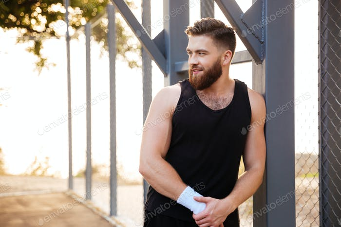 Smiling bearded athlete standing outdoors and looking away