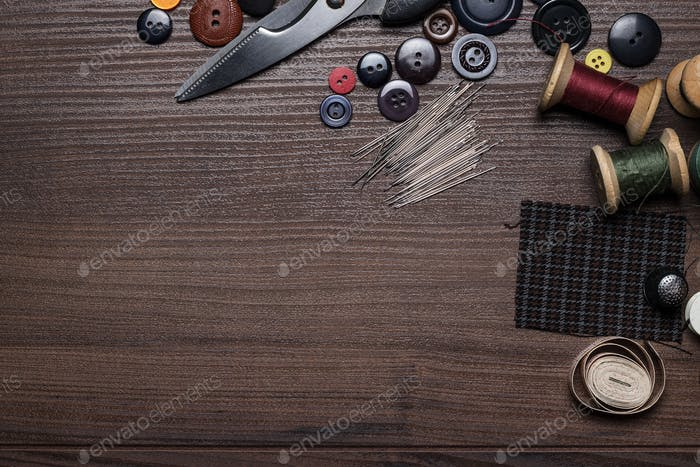 Needles Threads And Buttons  On Brown Wooden Table