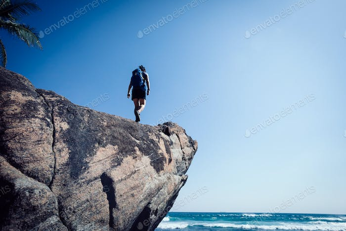 Brave woman backpacker walking on the cliff edge at seaside