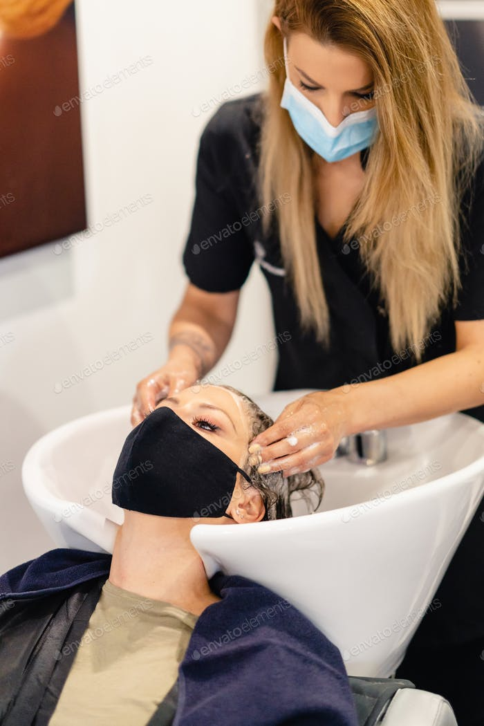 Female hairdresser washing a client's head in a salon, protected by a mask