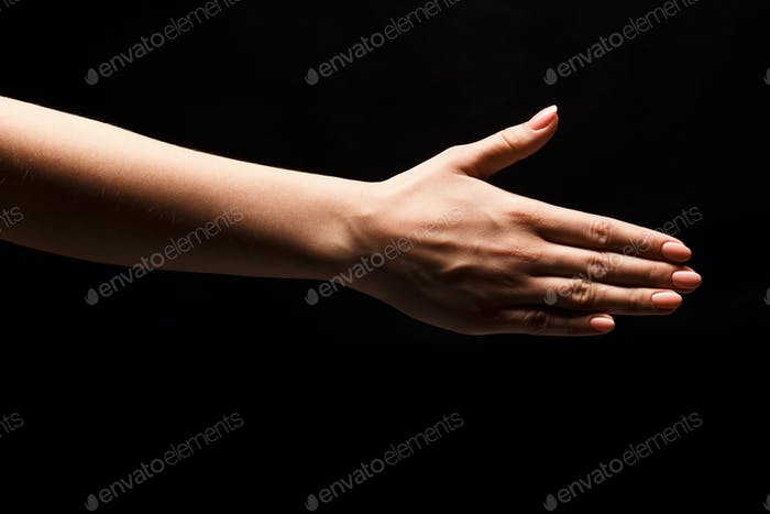 Hand ready for handshake isolated on black