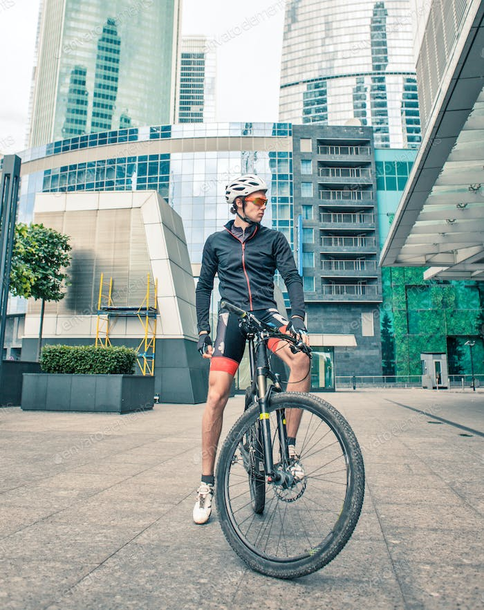 sportsman cyclist stay with bicycle at street among skyscrapers