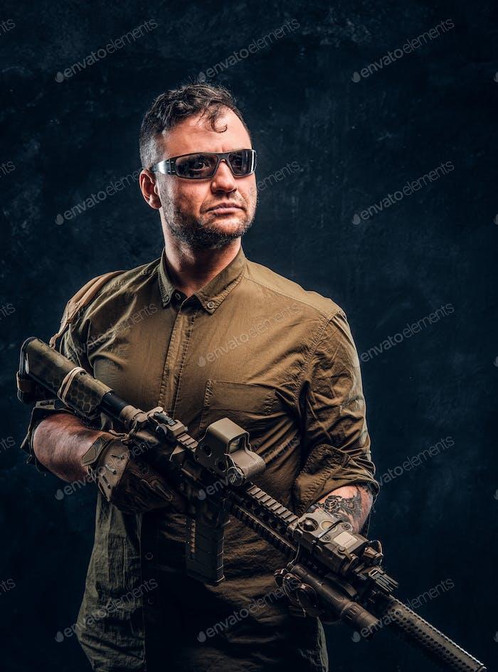 Portrait of a stylish man wearing shirt sunglasses holding assault rifle and looking sideways.