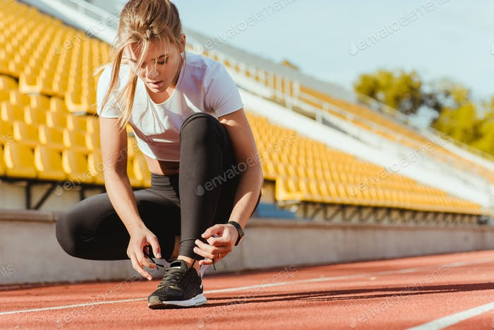 Woman tie shoelaces at outdoor stadium