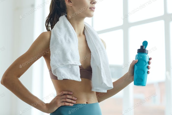 Young Woman Holding Water Bottle after Workout