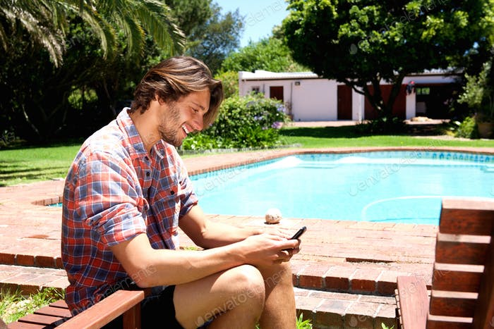 handsome man smiling with cell phone next to pool