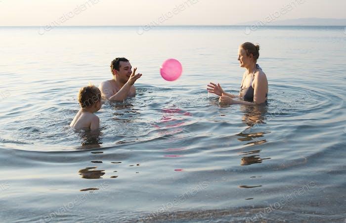 Junge Familie spielen mit Ball bei Sonnenuntergang